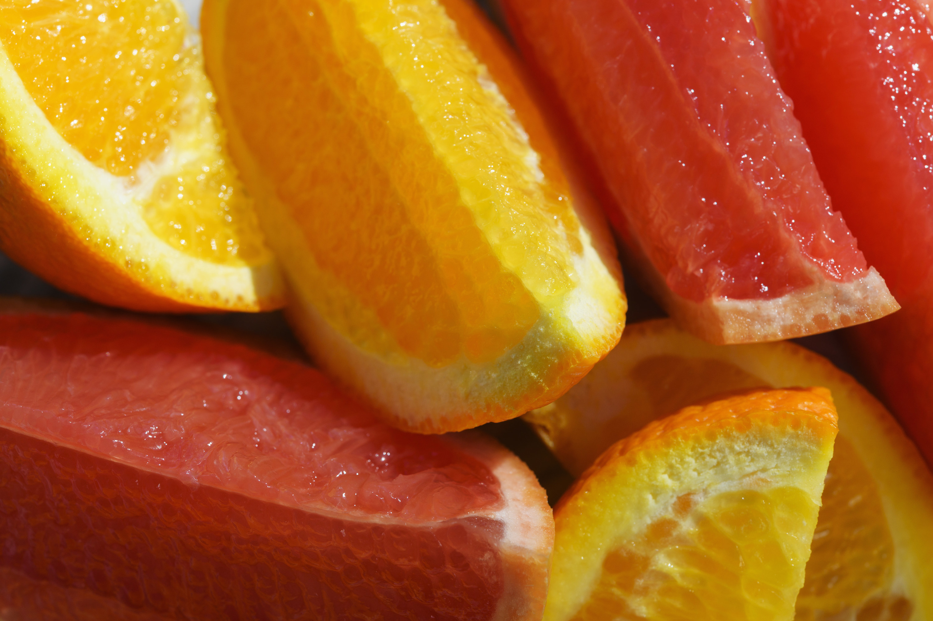 Close-up of yellow and red slices of citrus fruit.