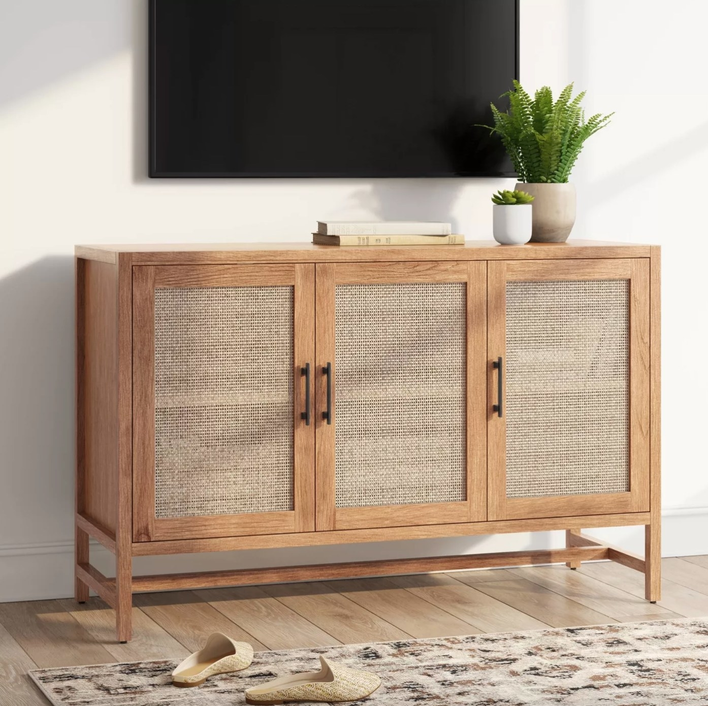 The three-door accent TV stand in natural holding books and plants