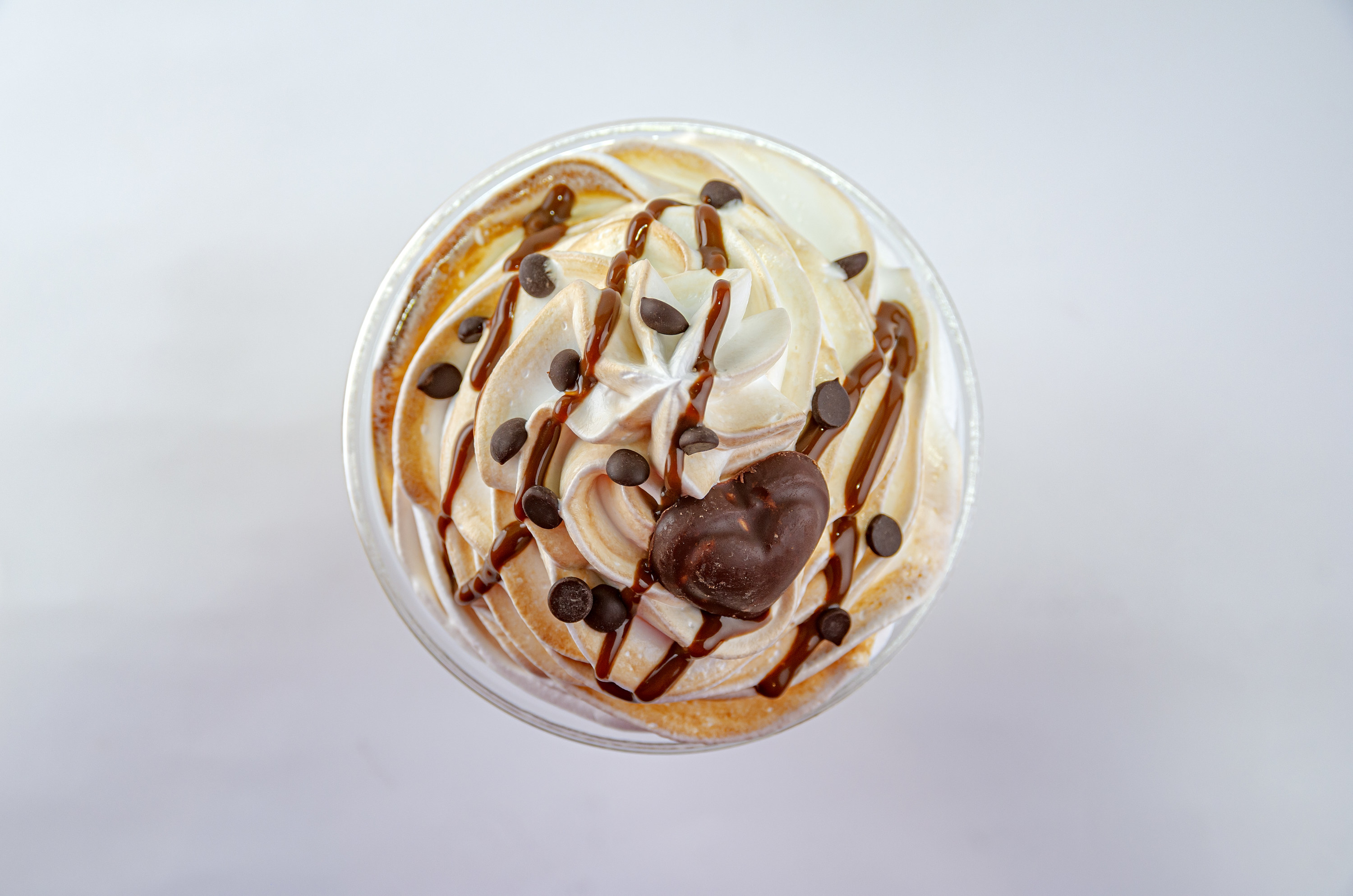 Aerial shot of a Frappucino drizzled with dark chocolate chips, chocolate syrup, and a heart-shaped chocolate piece.