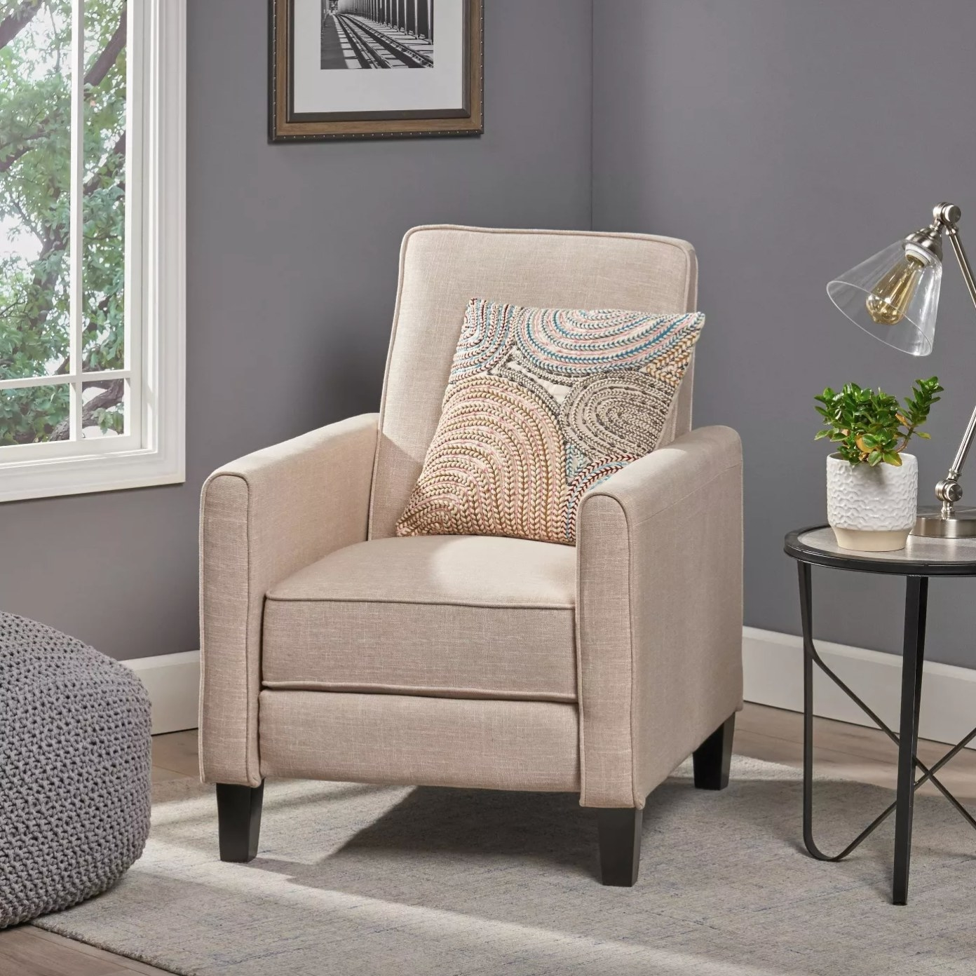 The fabric recliner club chair in beige with black legs holding a swirly patterned pillow