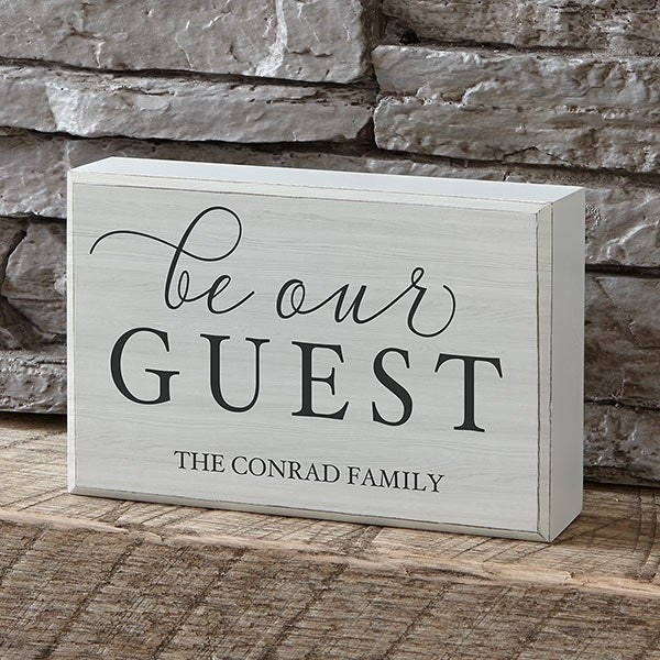 """a white block that says """"be our guest"""" with """"the conrad family"""" under it"""