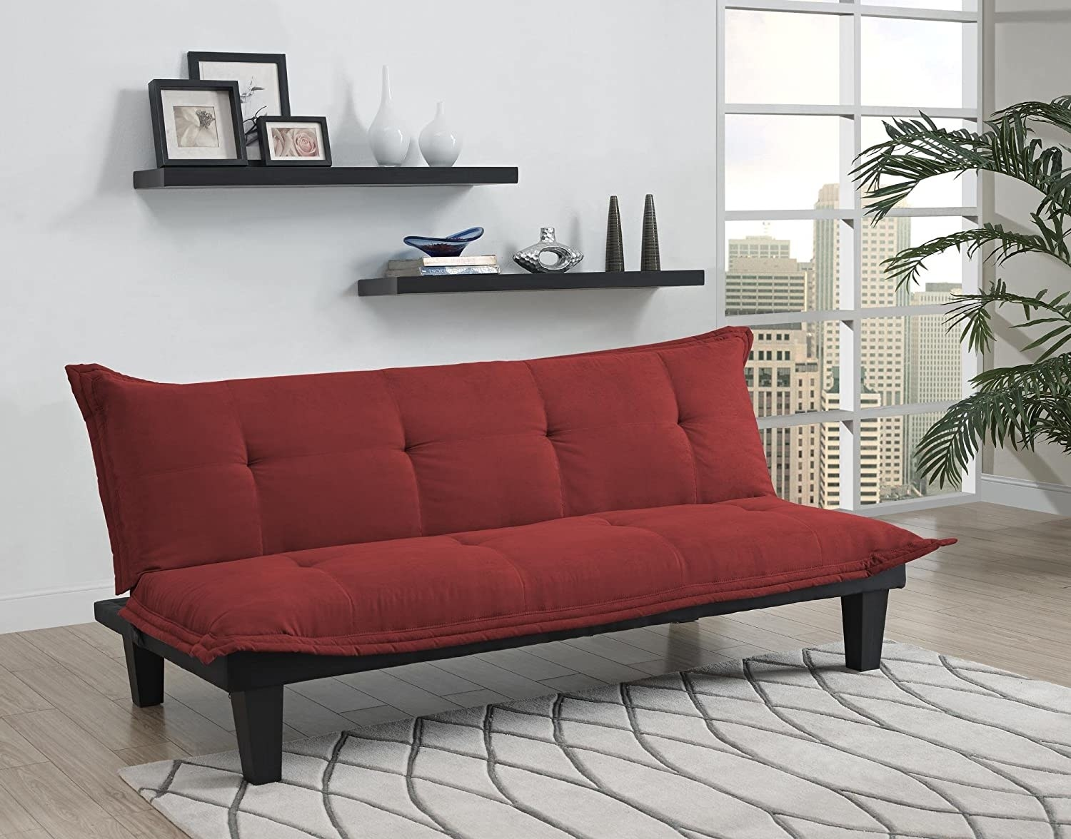 a red futon with a tufted back and seat