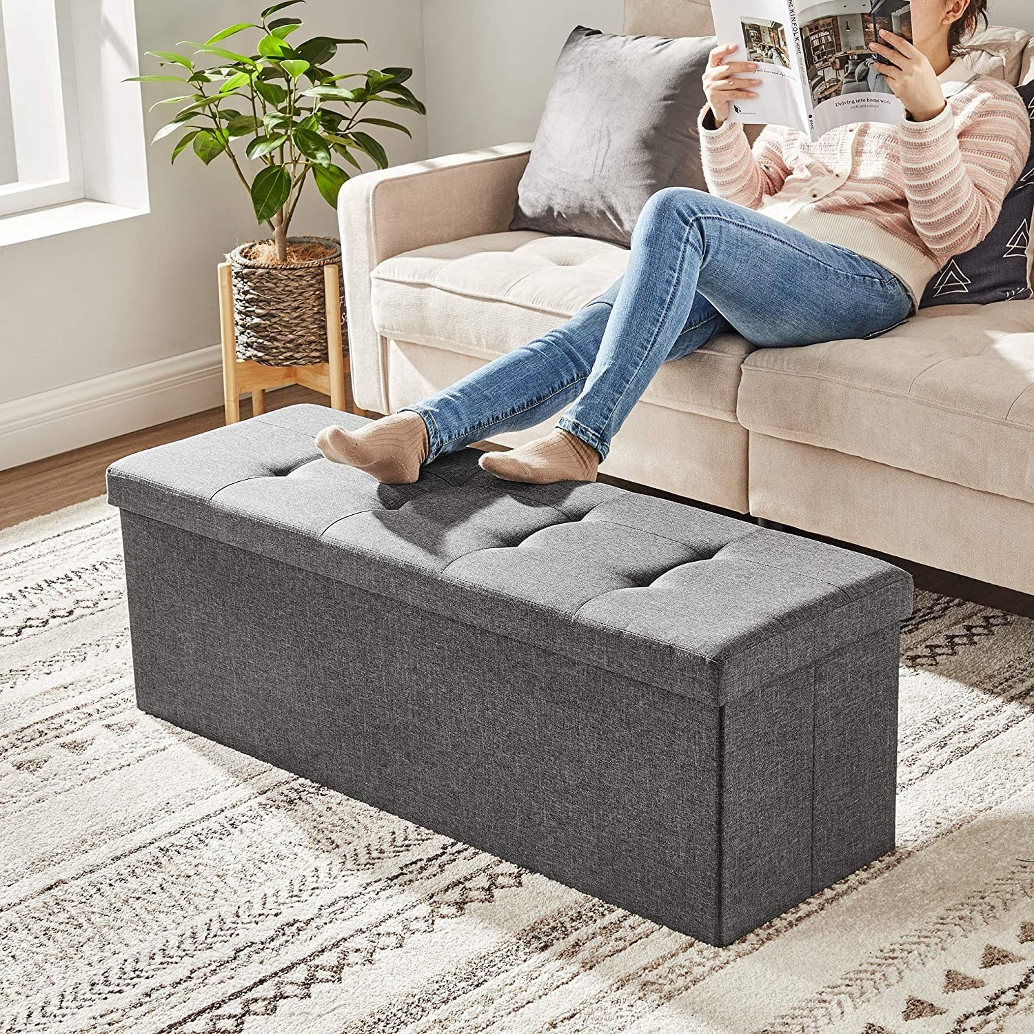person sitting on couch reading with feet up on the long storage ottoman