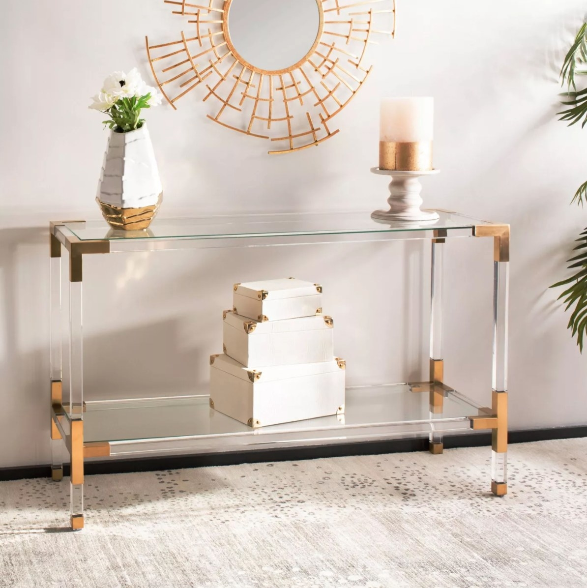 The console table in glass with gold corners holding a vase of flowers and candles