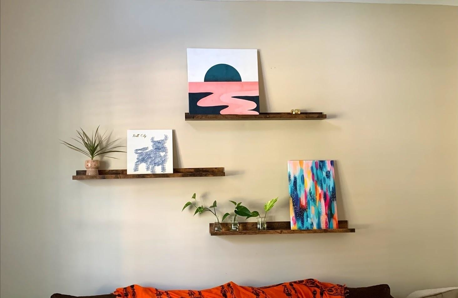the floating shelves in a living room above a couch