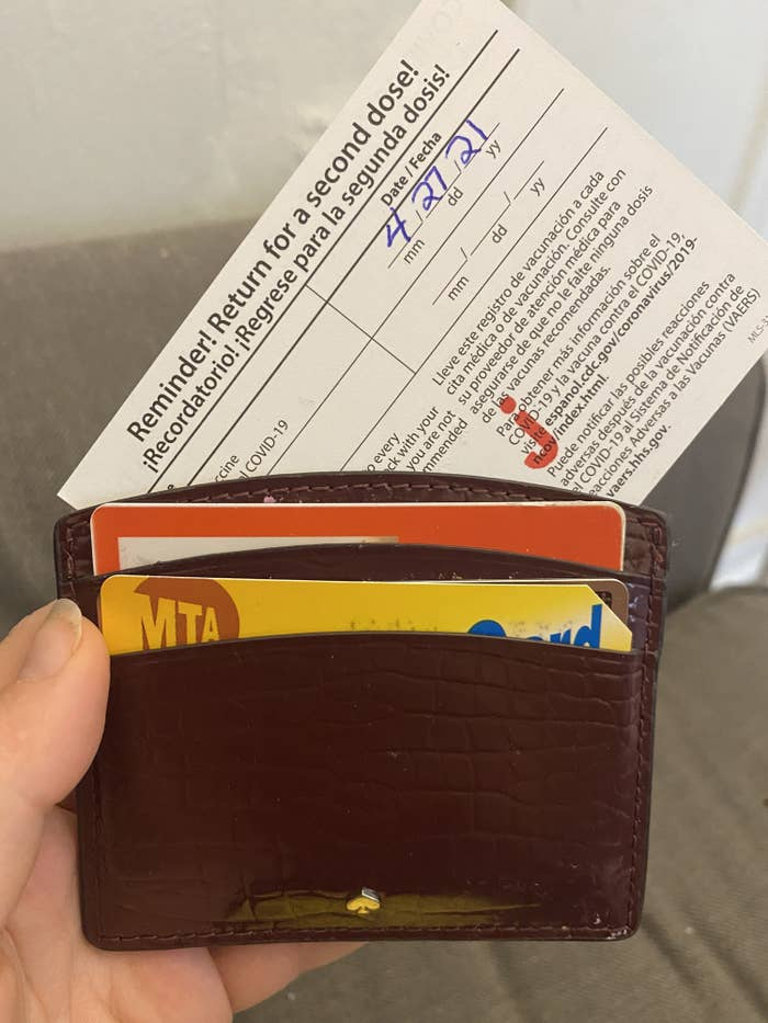 BuzzFeed editor attempting to put a too big vaccine card in a wallet