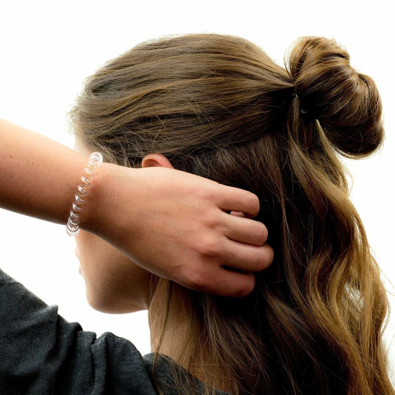 model with top half of hair up in a messy bun and the phone cord-like band on wrist