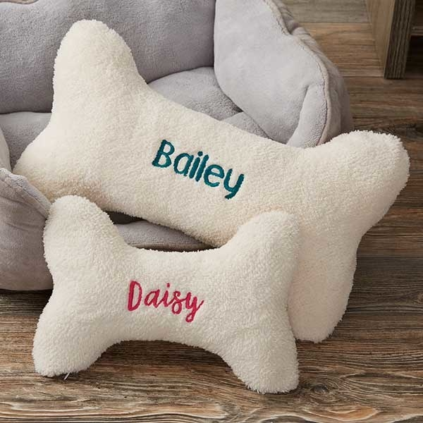 Two cream dog bone-shaped pillows, one says Bailey and the other smaller one says Daisy