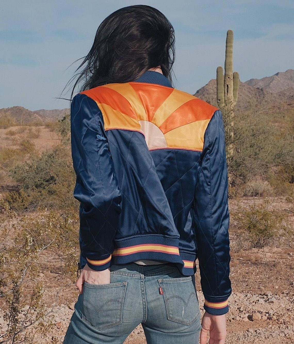 A model wearing the bomber jacket with jeans in the desert