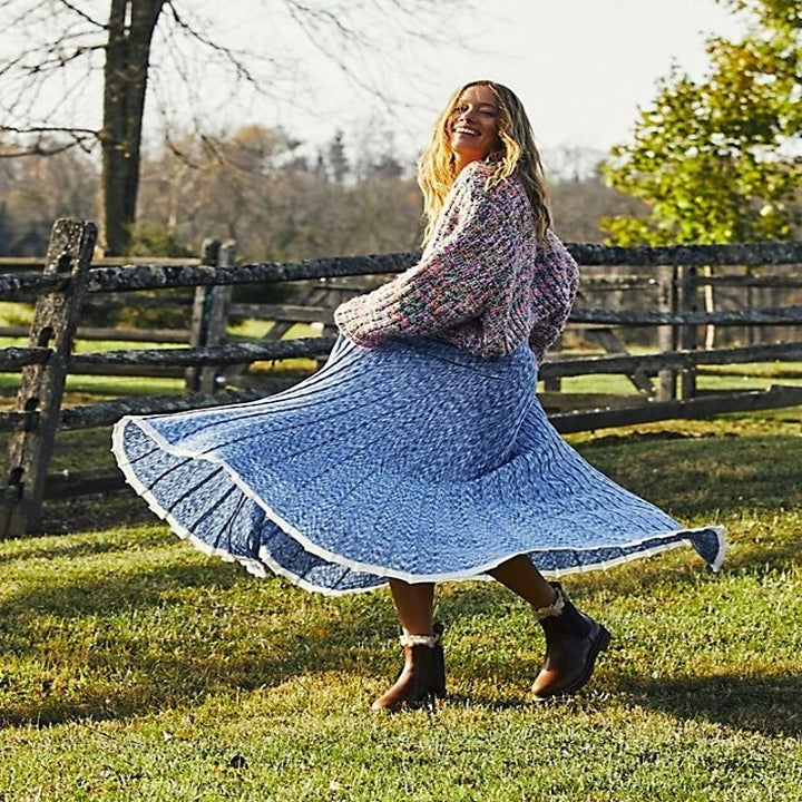a model twirling in the knit maxi skirt paired with a sweater