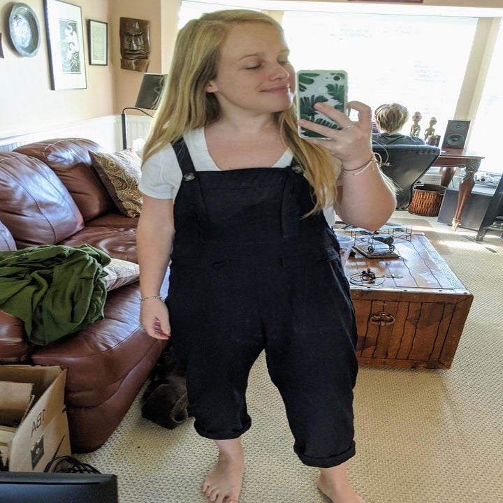 a reviewer mirror selfie of someone wearing a white T-shirt under the overalls in black