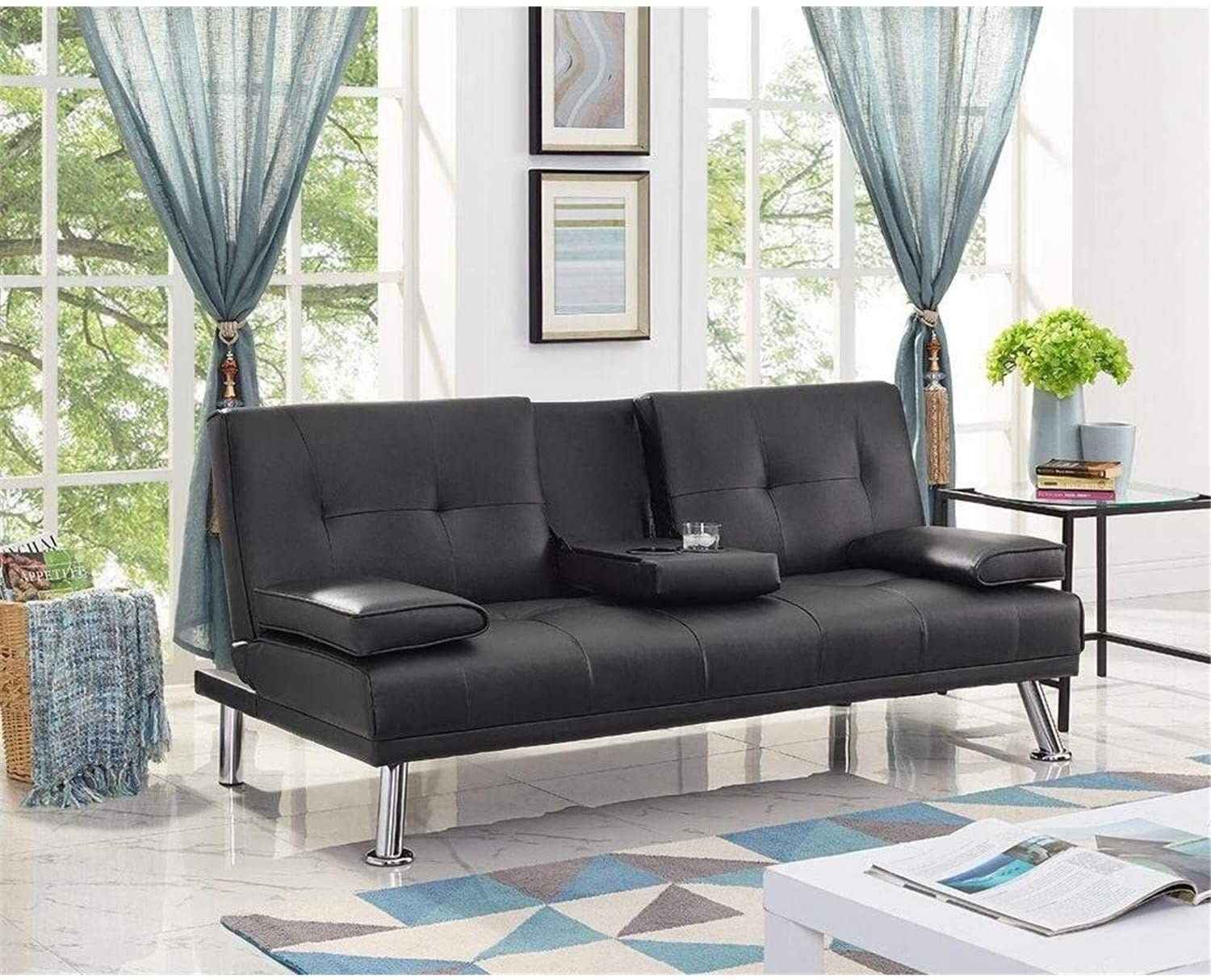 a faux leather black futon with chrome legs and a fold down cup holder