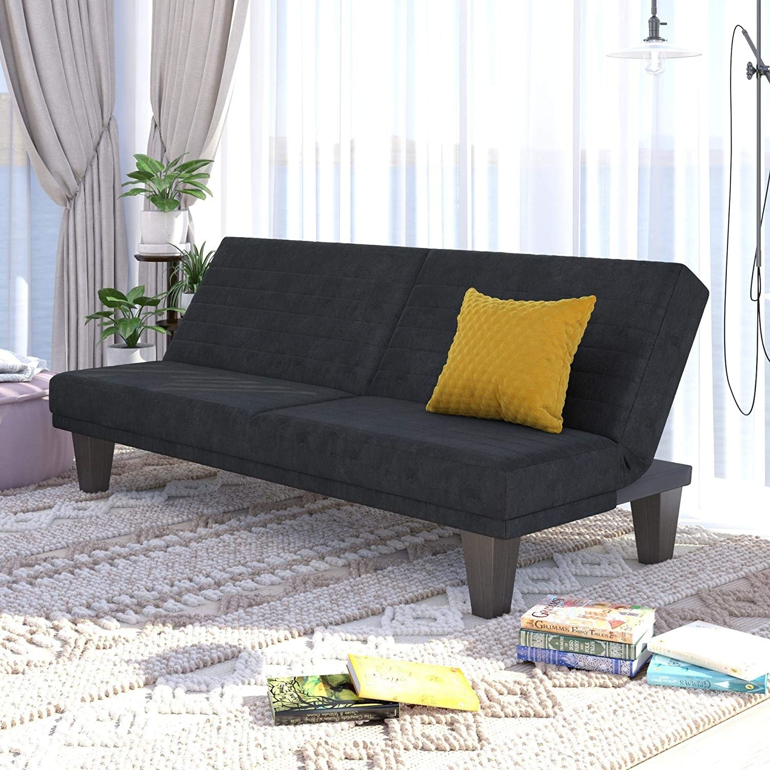 a black angled futon couch with a yellow pillow on it