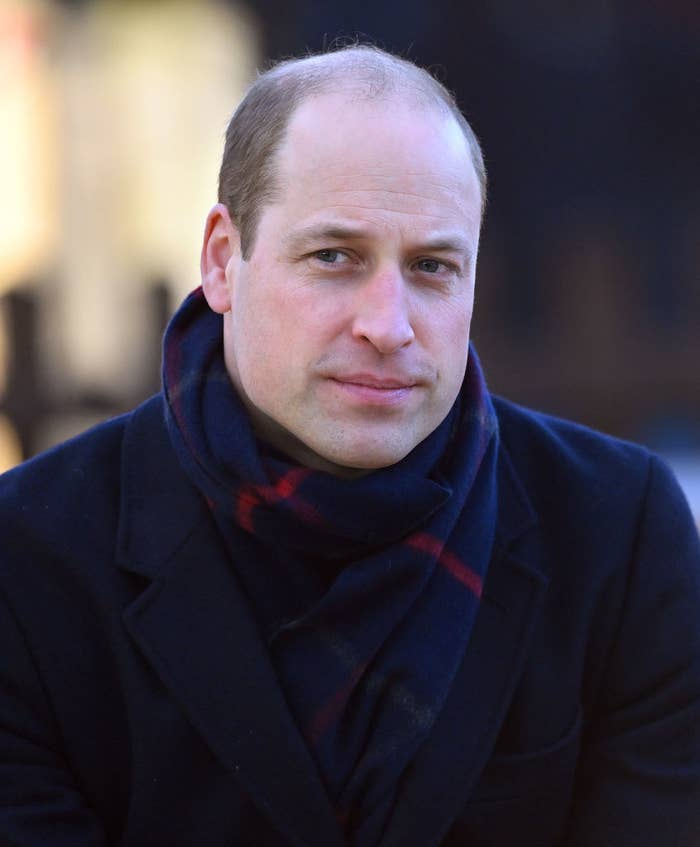 A balding Prince William in a coat and scarf