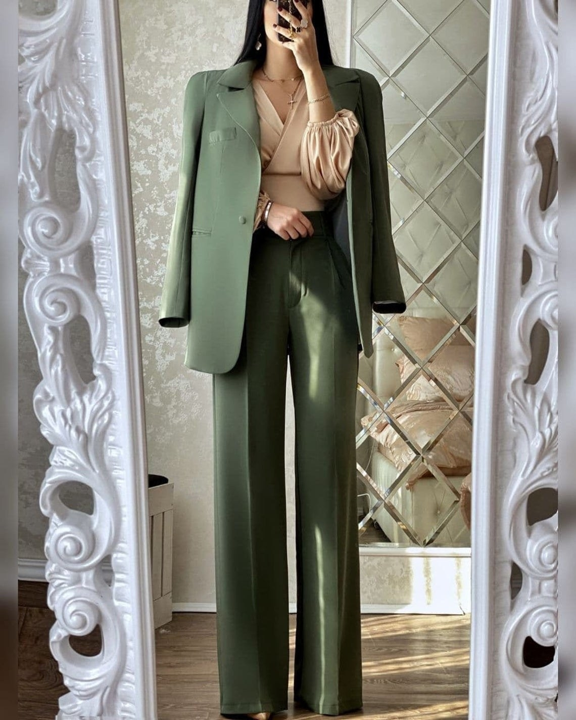 A model taking a mirror selfie in the green suit