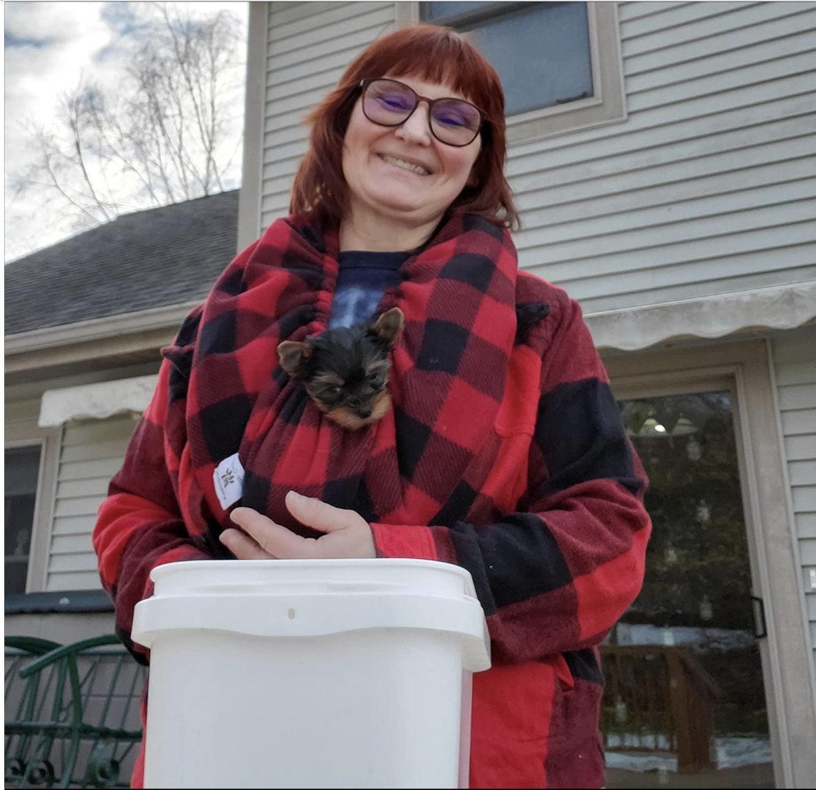 Reviewer wearing black and red gingham scarf with a Yorkie in it