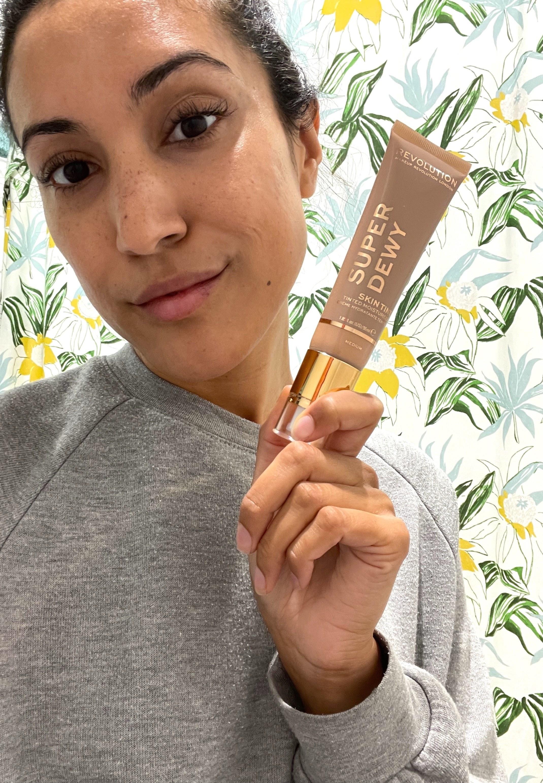 Jasmin holding the tube of tinted moisturizer in shade Medium
