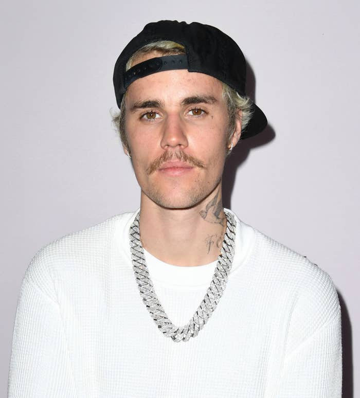 Justin wearing a sweater, baseball cap, and diamond chain necklace
