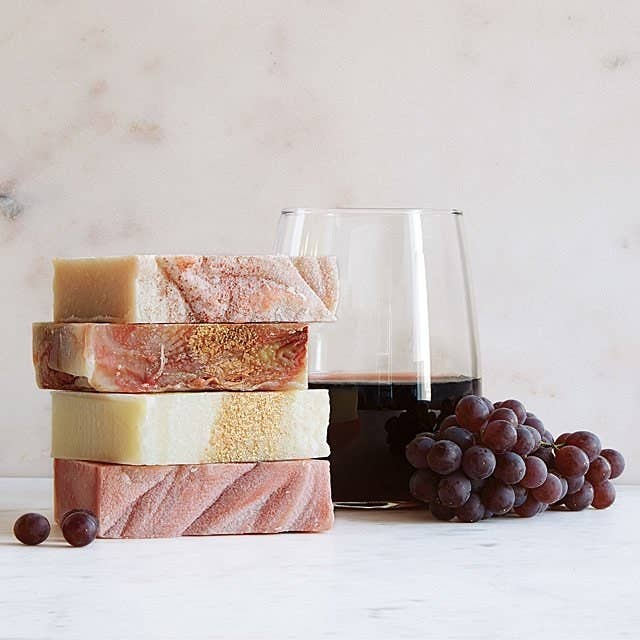 wine soaps stacked up next to glass of wine and grapes