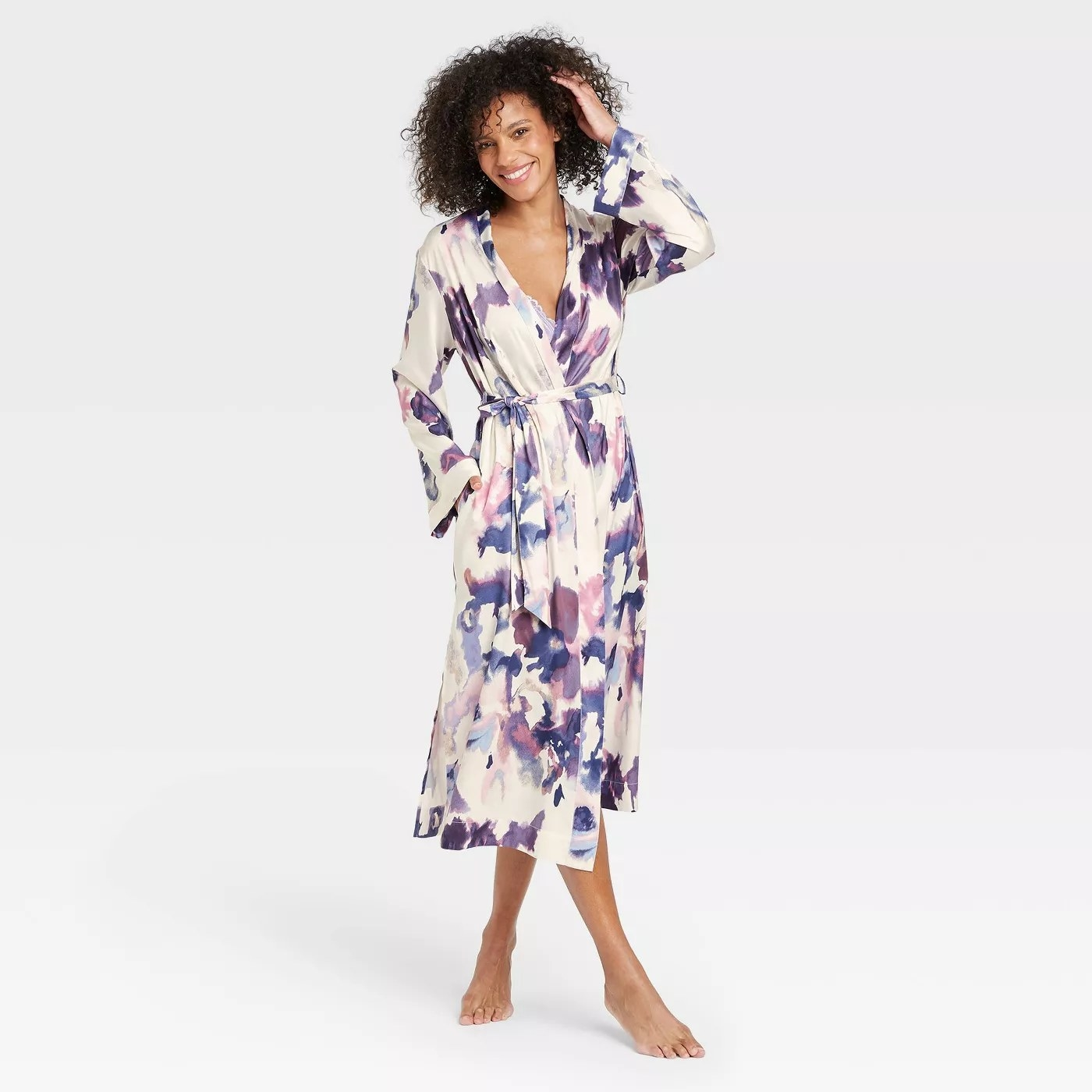 A model wearing the cream-colored robe with a purple floral print and matching waist tie
