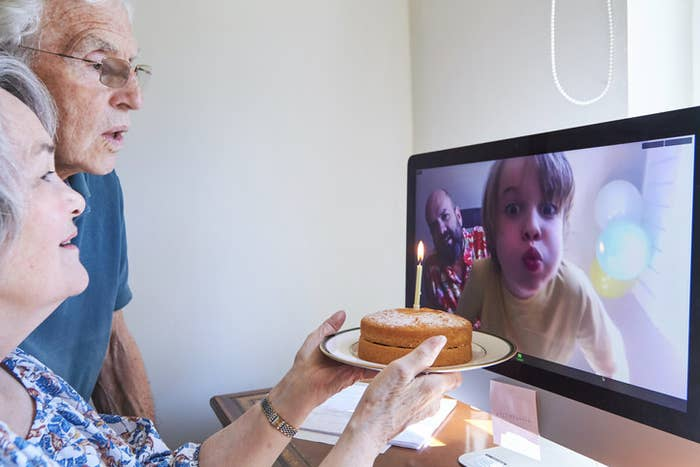 grandparents facetiming with grandkid with a cake as the child pretends to blow out candles