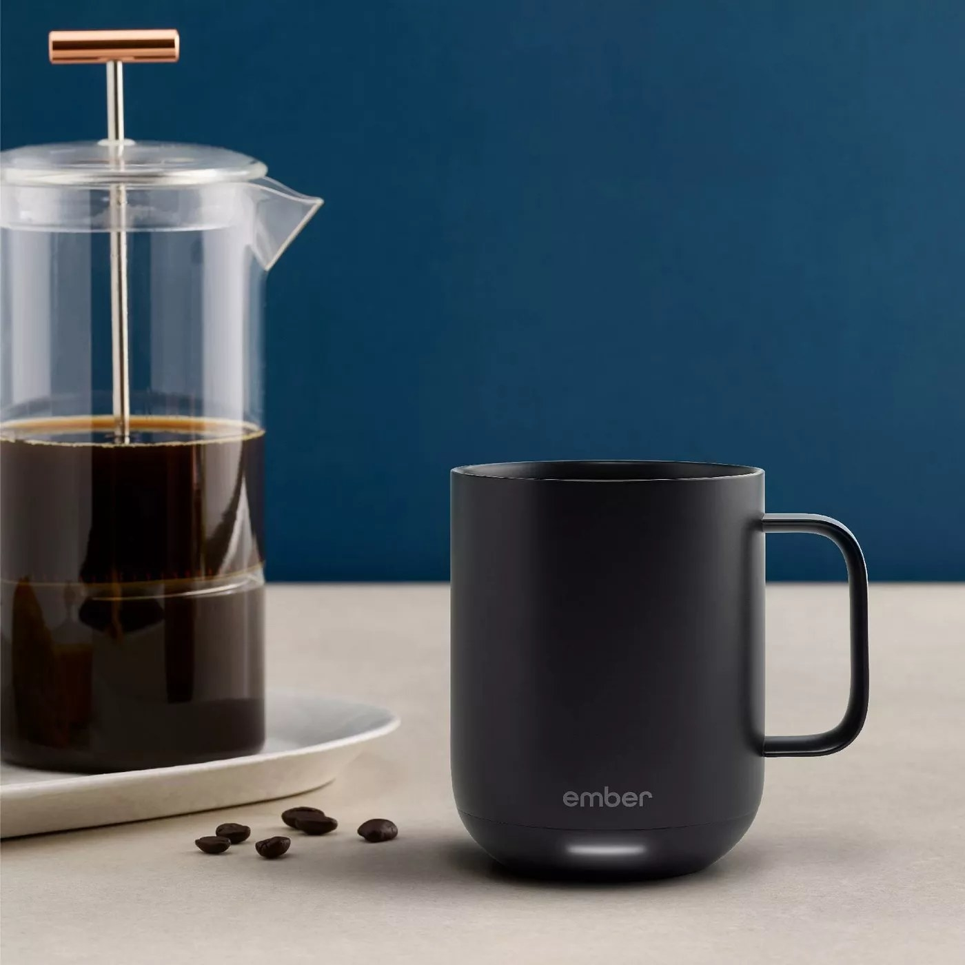 The mug with a sensor on the bottom next to a French press filled with coffee in a kitchen