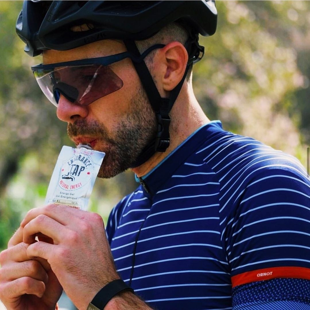 Someone squeezing the energy gel into their mouth while wearing full cycling gear