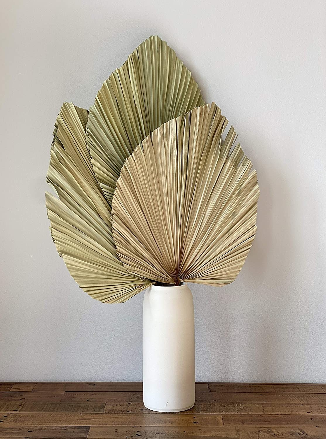 Three dried palm leaves in a white vase