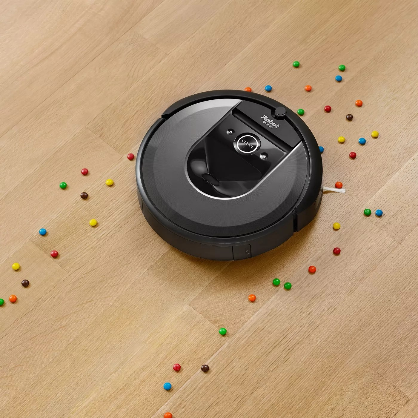 The Roomba picking up food on a wooden floor