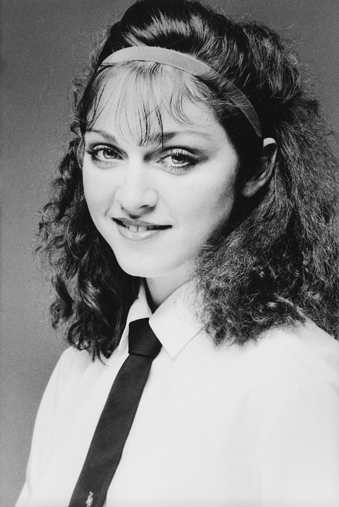 With brown hair and bangs and wearing a tie