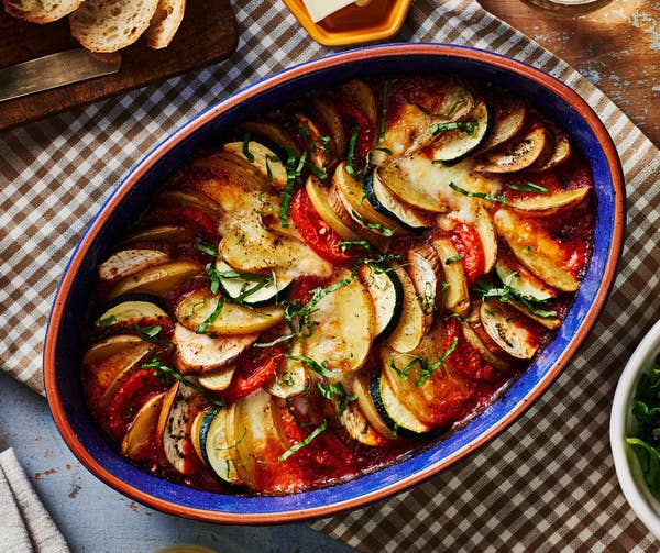 A ceramic baking dish with a beautifully arranged garden vegetable ratatouille, garnished with fresh herbs.