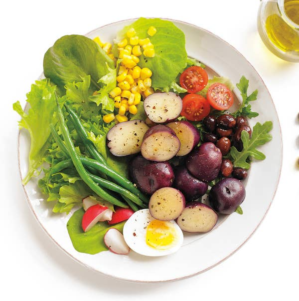 An arranged niçoise salad: little potatoes, half a boiled egg, olives, cherry tomatoes, green beans, sweet corn, and radishes on a bed of lettuce.