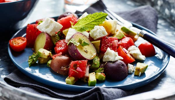 A plate piled with chopped watermelon, little potatoes, avocado, feta, mint, and cherry tomatoes.