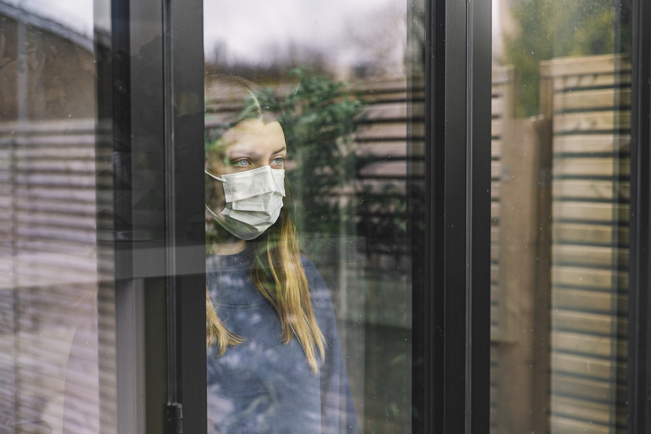 woman in mask looking out a window