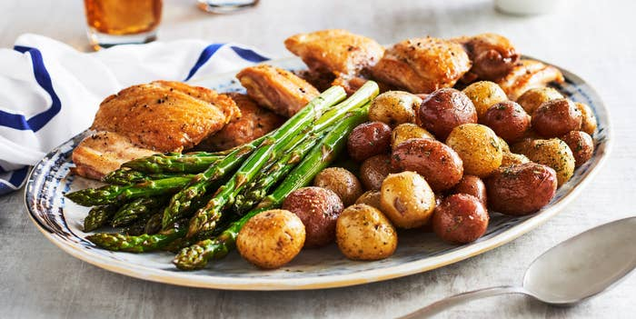A big plate of sheet pan–roasted whole seasoned little potatoes, asparagus, and chicken.