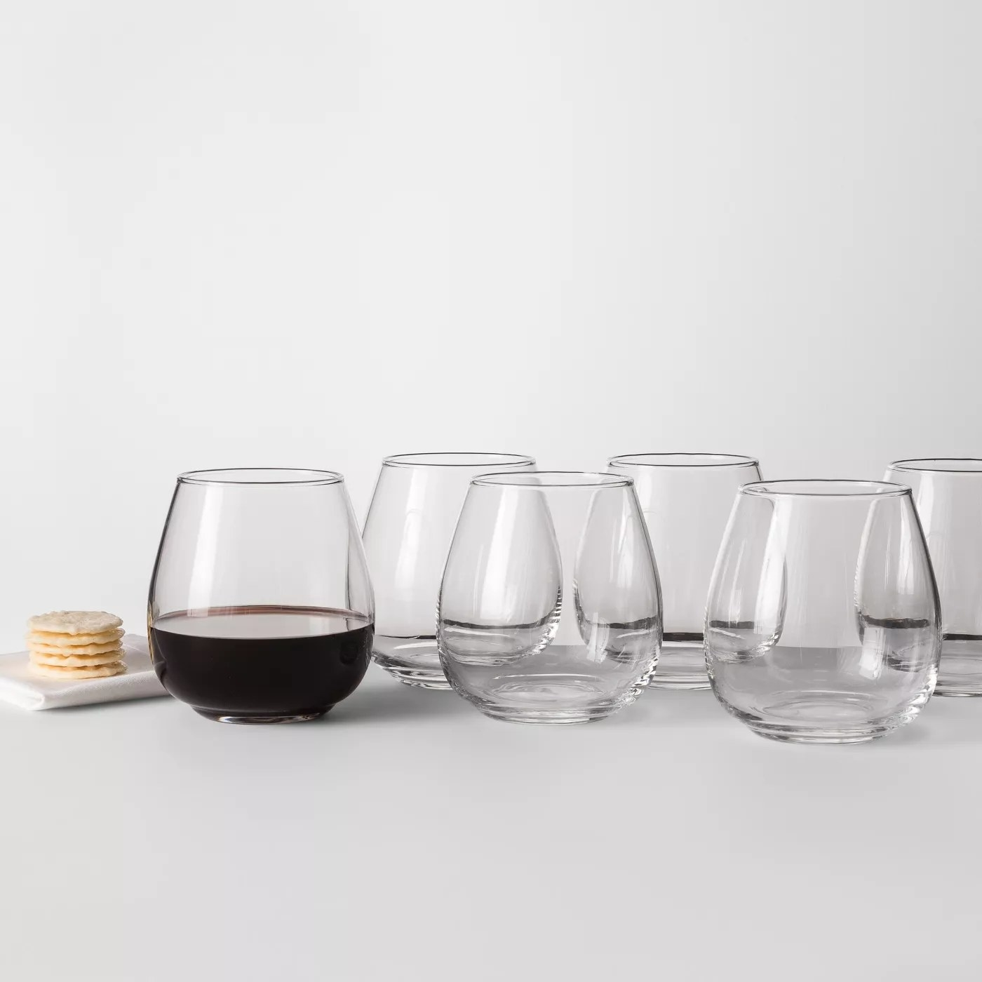 The stemless wine glass set, including one filled with red wine, on a table
