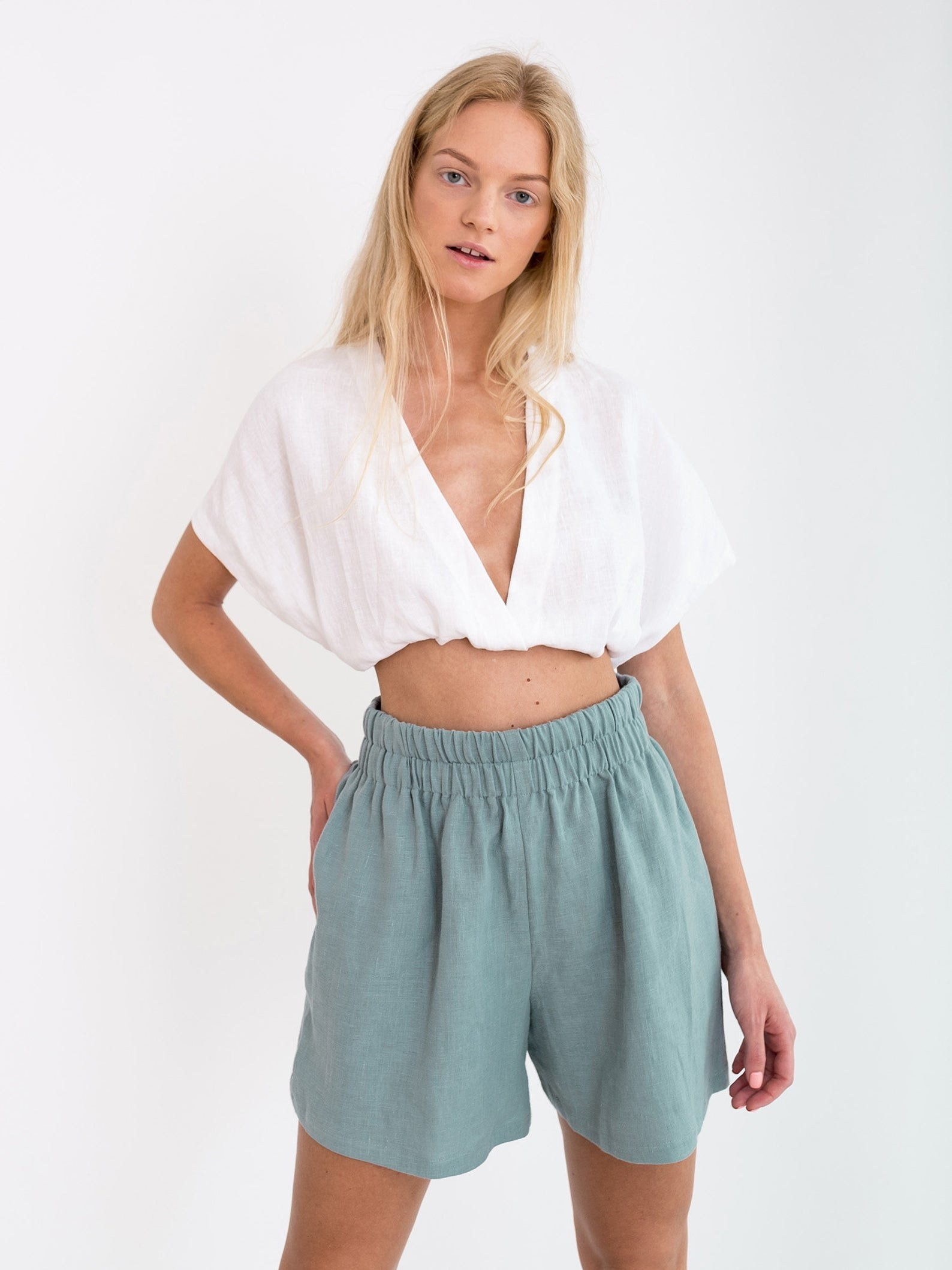 model wearing the dark turquoise isla high waisted linen shorts with a white crop top