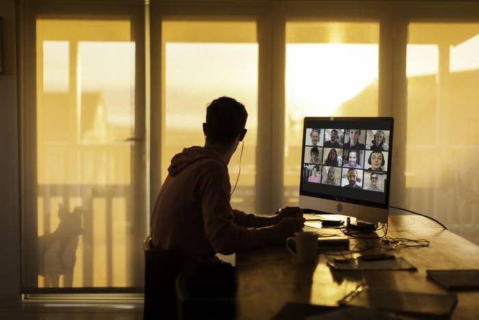 man in shadows looking out the window on a zoom call