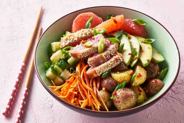 A bowl of poke with sesame-crusted tuna, julienned carrot, avocado, chopped cucumber, grapefruit, roasted little potatoes, and a spicy dressing.