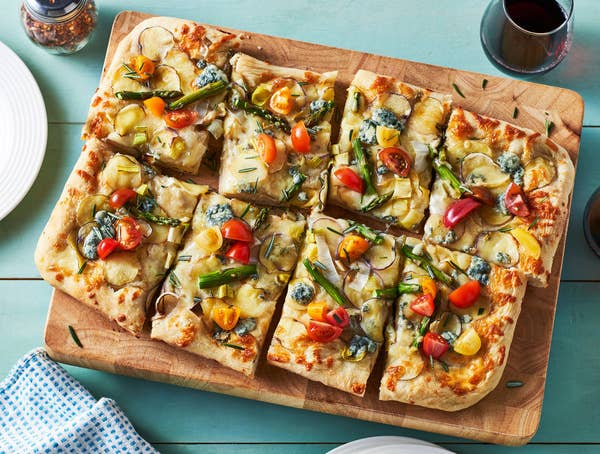 A rectangular pizza topped with potatoes and other vegetables, served on a wooden board.
