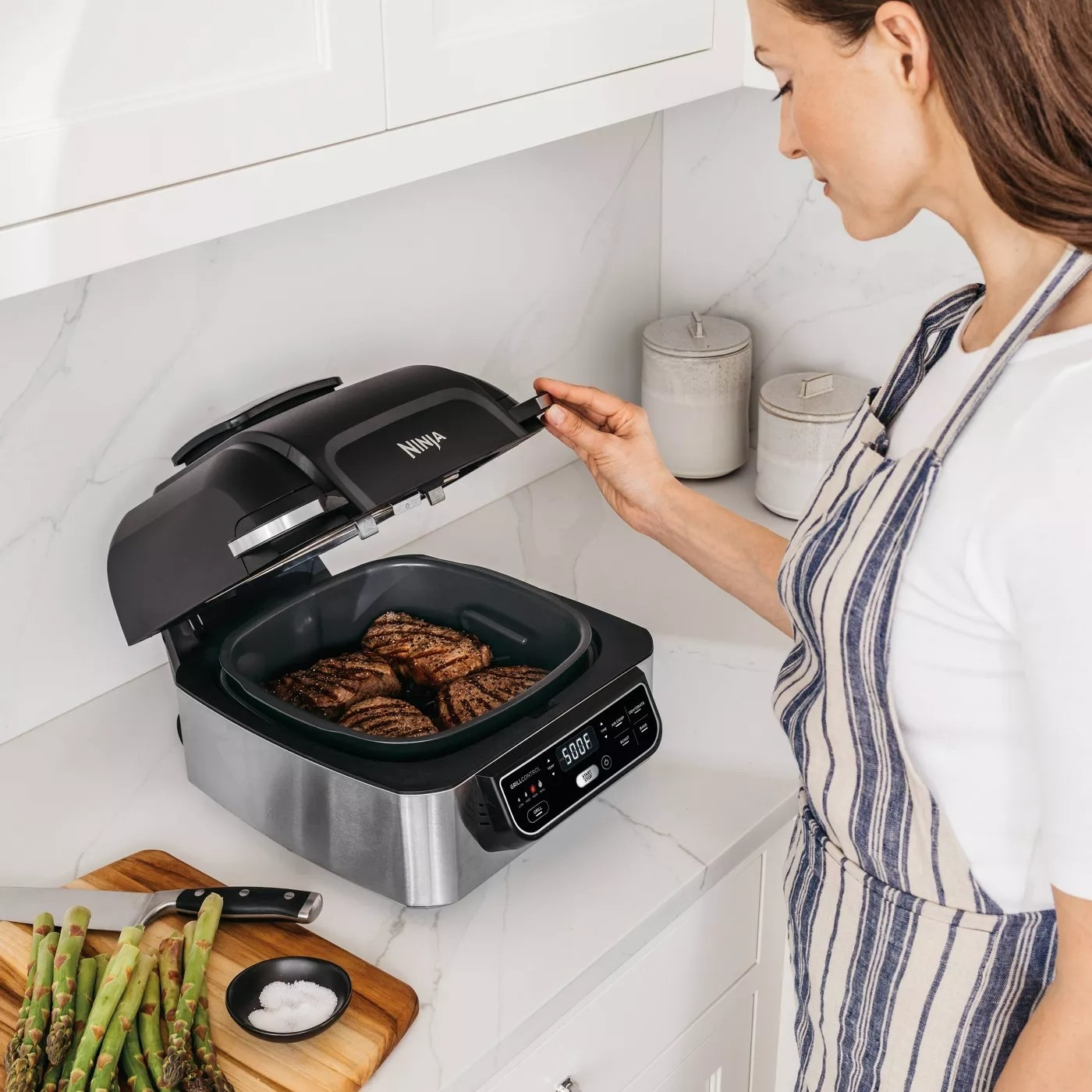 A model using the grill to make steak in a kitchen