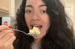 Woman taking a bite of popcorn salad