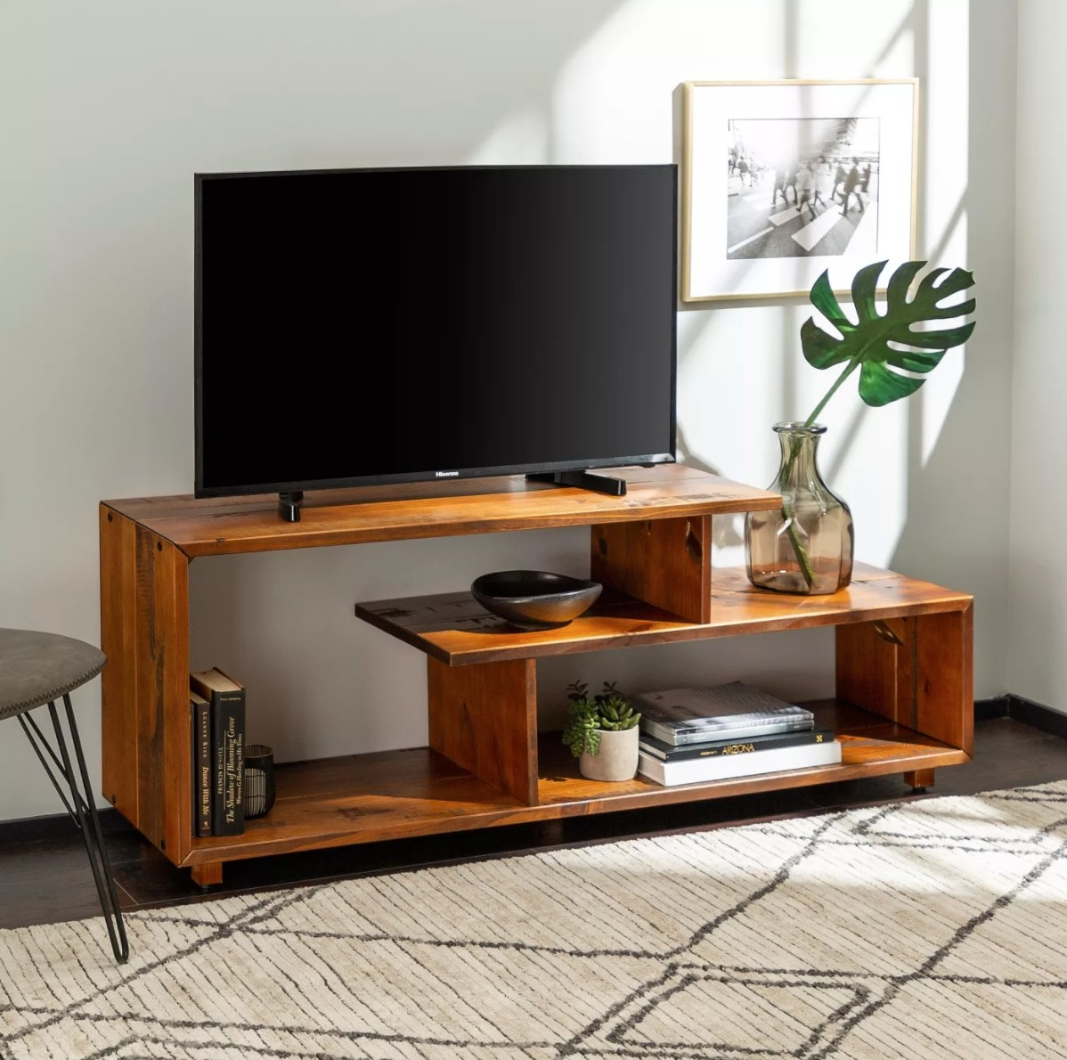The rustic solid wood TV stand holding a flat-screen, planter, books, and a vase with a monstera leaf