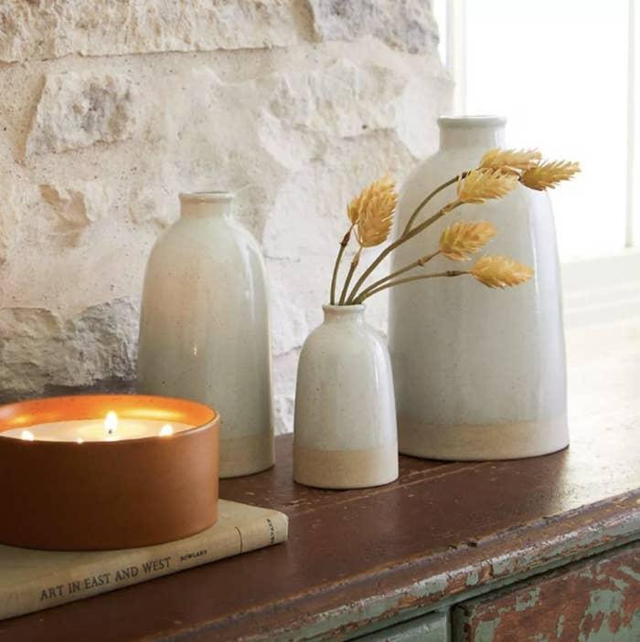 three ceramic stoneware vases on a ledge