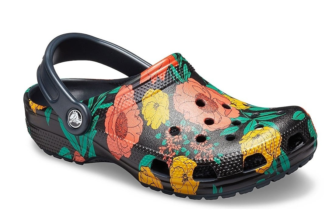 Black Crocs rubber clogs with holes and an orange, yellow, and green floral print