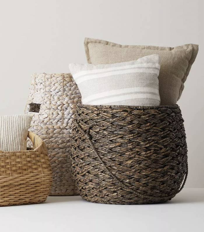 a large brown wicker basket holding pillows inside