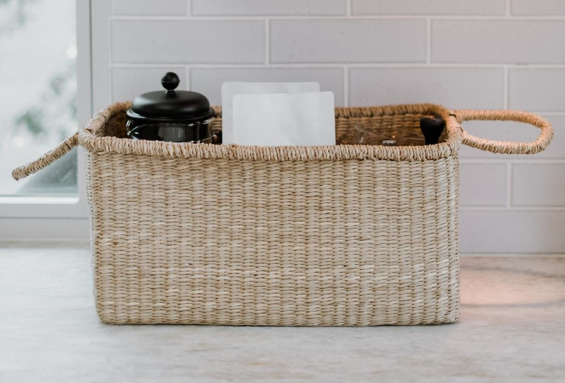 rectangular woven basket with handles on either end; a french press coffee maker and a bag of coffee grounds poke maybe an inch or two out of the open top
