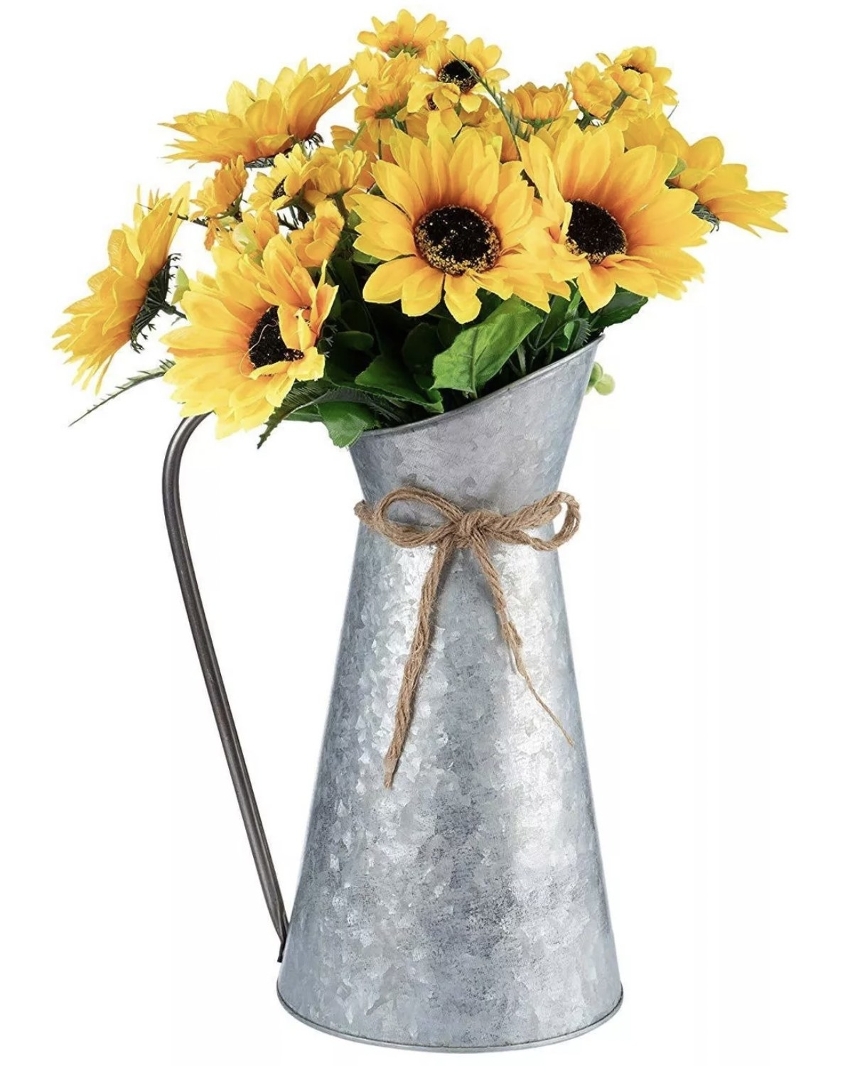 a silver metal pitcher holding a bouquet of daisies