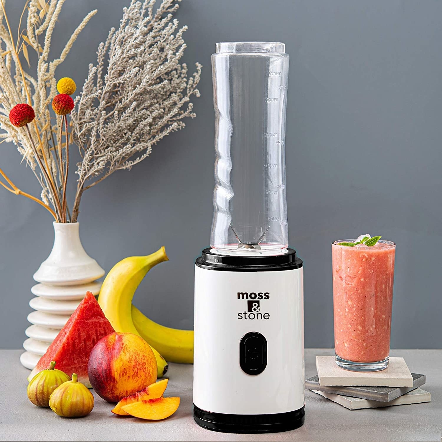 A slim person blender next to a smoothie and some fresh fruit