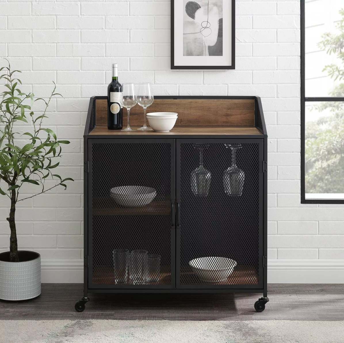 The industrial mesh cart in rustic oak holding wine glasses, a bottle of red, and white bowls